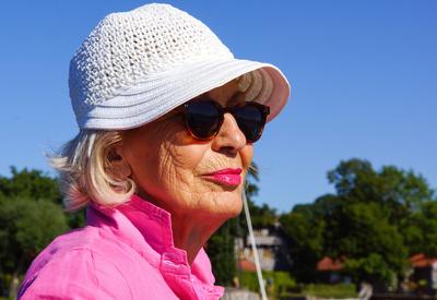 Seniorin mit Sonnenhut und Sonnenbrille - Golden Agers oder Abzocker?