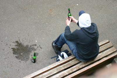 Junger Mann mit Bier auf einer Bank