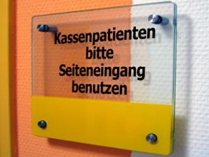 Schild mit dem Text: Kassenpatienten bitte Seiteneingang benützen