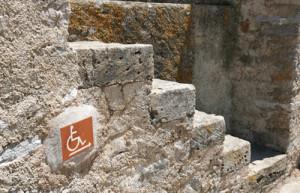 Treppe mit einem Hinweisschild für Rollifahrer