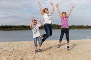 Frau udn zwei Kinder hüpfen am Strand